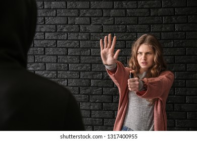 Woman with pepper spray defending herself against thief on dark background