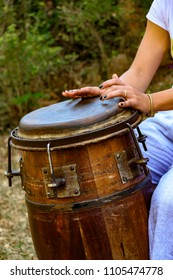 Woman percussionist hands playing a drum called atabaque during brazilian folk music performance