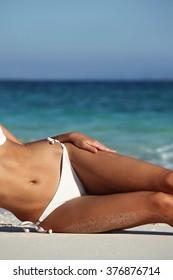 Woman with perfect body in bikini lying on beach over blue sea background