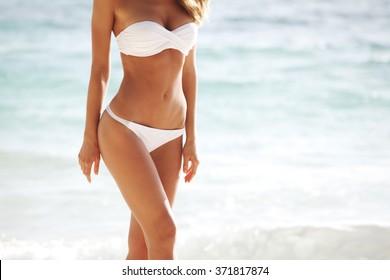 Woman with perfect body in bikini on sea background
