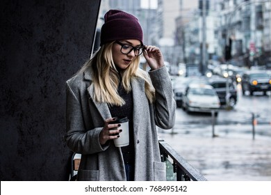 Woman with perfect city style. Portrait of stylish hipster girl in coat holding glasses and looking down while standing outdoors. Young woman in eyeglasses drinking coffee. Urban fashion