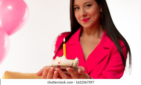 woman with perfect makeup and pink lipstick sitting near air balloons with confetti and smiling. Holding cake with a candle. Concept celebrating, party, birthday