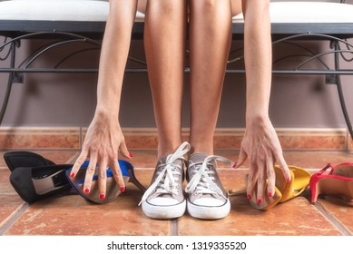 Woman with perfect slim legs, choosing comfortable sneakers rather than uncomfortable high heels shoes .