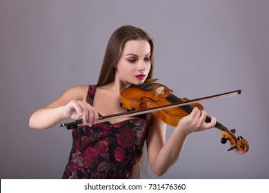 Woman performer with violin in studio over gray background