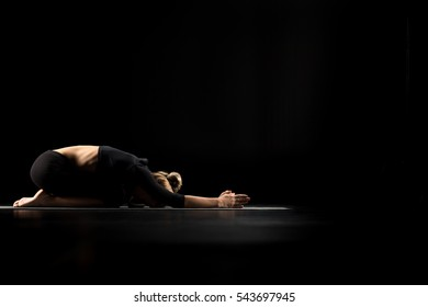 Woman performing Balasana or Childs Pose on yoga mat isolated on black