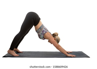 Woman performing Downward-Facing Dog yoga pose on a yoga mat isolated on a white background