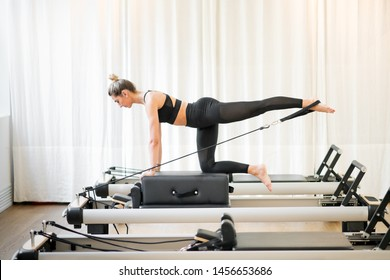 Woman performing a pilates diagonal stabilisation exercise using a strap on a reformer bed in a gym in a health and fitness concept