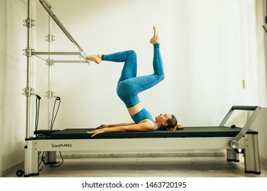 Woman performing Pilates exercise using a Cadillac or Trapeze table