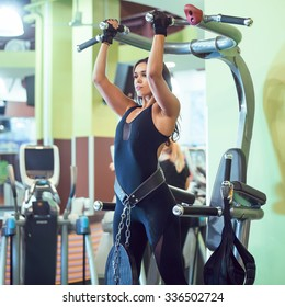 Woman performing pull ups in a bar at gym