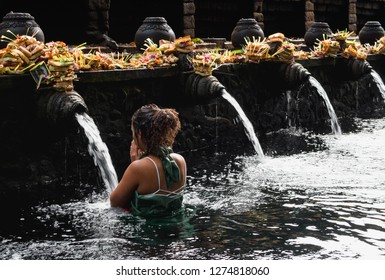 WOMAN PERFORMING WATER PURIFICATION CEREMONY AT TIRTA EMPUL, UBUD, BALI, INDONESIA