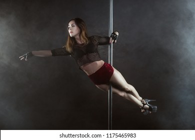 Woman performs a dance of a striptease on a pole, she shows the show.