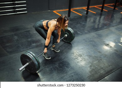 Woman performs deadlift with weight in the gym
