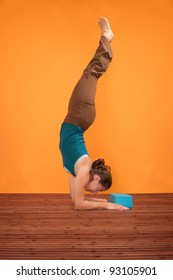 Woman performs Feathered Peacock Yoga Pose over orange background