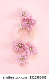 Woman perfume among flowers on pink background. Top view point, flat lay.