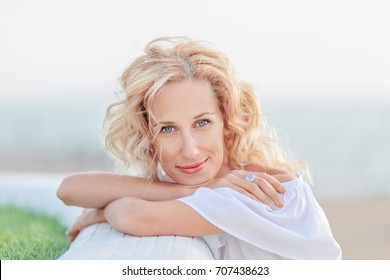 A woman in the period of menopause/ Blond mature woman against the sky and grass background