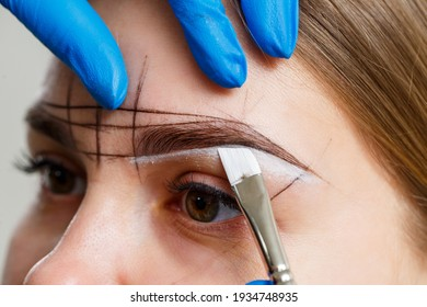 A woman permanent makeup artist draws a sketch of the eyebrows on the face of her client.