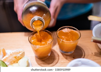 Woman person serving pouring kombucha fermented tea into two juice shot glasses on wooden table from bottle
