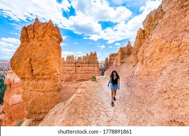 Woman person walking by orange rock formations at Queens Garden Navajo Loop trail at Bryce Canyon National Park in Utah with camera happy on footpath