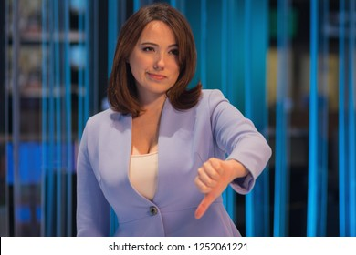 Woman with pessimistic emotion in a television studio shows a gesture of fingers to the bottom. People