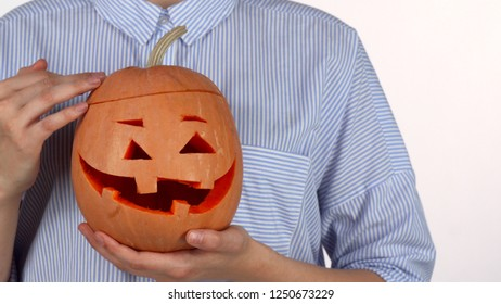 Woman petting Halloween pumpkin isolated on white