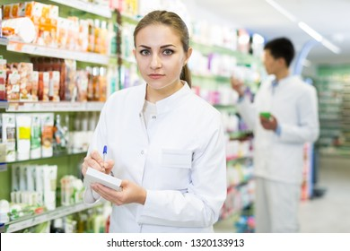 Woman pharmacist is inventorying medicaments with notebook near shelves in apothecary.