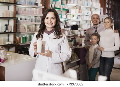 Woman pharmacist standing with a cash desk in the pharmacy and helping customers