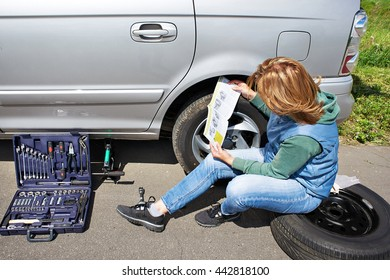 Woman with phone is calling in service of spare tire his car  and reading owner's manual