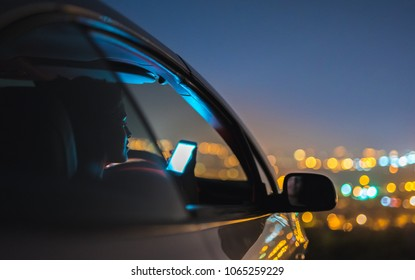 The woman phone in a car on the background of city lights. evening night time