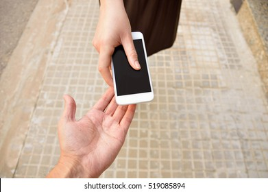 woman with a phone in his hand  return it to its owner at the city street. Concept of loan from a phone to help someone.