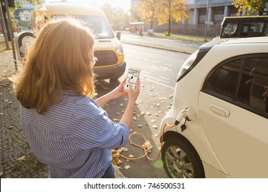 Woman with phone on a background of electric cars charging point. E-car sharing concept