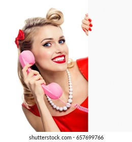 Woman with phone, in pin-up style dress, showing blank signboard with copyspace area, isolated over white background. Caucasian blond model posing in retro fashion and vintage concept studio shoot.
