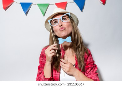 Woman in a Photo Booth party holding glasses and bow tie pouting lips