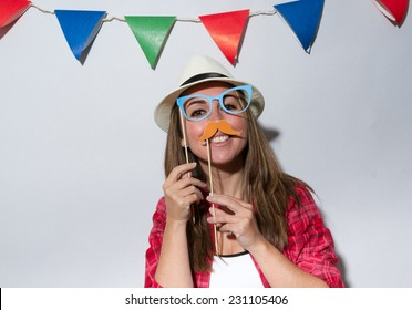 Woman in a Photo Booth party holding mustache and glasses with garland decoration background