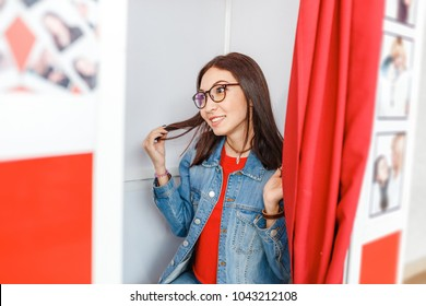 A woman is photographed and amused in a photo booth, making istant selfie photos for fun or for passport and documents
