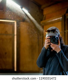 Woman photographer in dusty barn with sunbeams and glowing dust behind her as she takes a photo straight at the camera