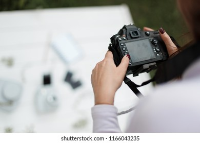 Woman photographer makes photos for stock photography. Female hands hold the camera close-up