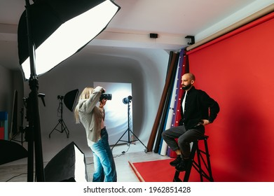 Woman photographer making business portraits for handsome bearded man on red background in photo studio. Work of a photographer. Backstage photo