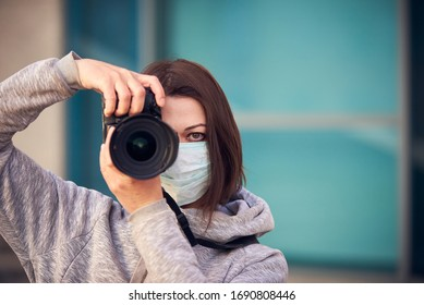 Woman photographer in mask with camera on street because epidemic of coronavirus in city. Protection against virus and infection.
