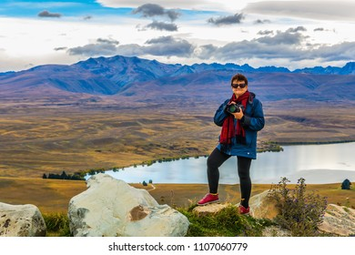 Woman photographer on the mountain. Exotic journey to the South Island, New Zealand. Concept of active and ecological tourism