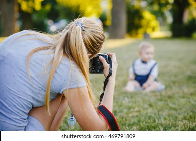 Woman photographer photographing the baby to spend outside in the park
