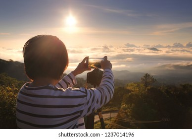 Woman photographer she is photographing the beautiful natural during sunrise time with a mobile phone at Tigers Head view point , Doi Inthanon National park,Chiang Mai in Thailand.