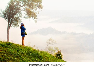 woman photographer standing at the mountain and mist