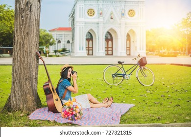 woman photographer take photo beautiful church by camera.Asian lady tourist relaxing near the tree on her holiday.