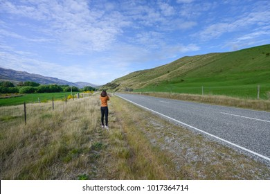 Woman photographer is take a photo at the highway roan in New Zealand