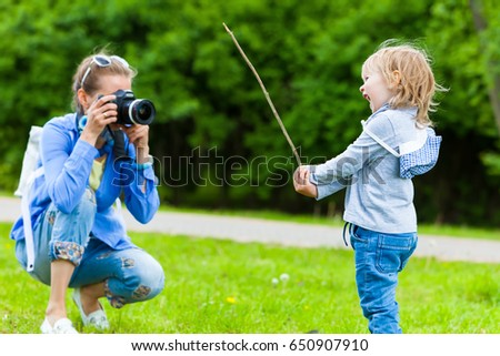Woman photographer takes pictures of a child in the park in summer