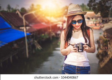 woman photographer taking photo during walk on walking street at market.tourist young lady have a good time on vacation. beautiful Asia woman traveler go to travel on holiday.