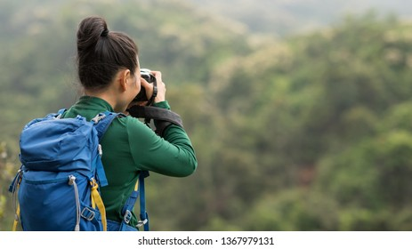 woman photographer taking photo on spring mountain forest