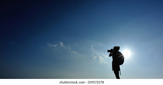 woman photographer taking photo on sunset
