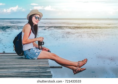 woman photographer taking photo for view of mangrove forest and the sea by camera.Asian lady  traveler sitting on the bridge in to the sea on her holiday.