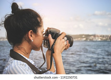 Woman photographer, taking pictures of landscape at sea
